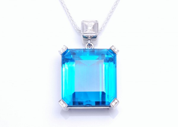 Blue topaz pendant with diamonds on the end of the claws, the work of a Custom Jewellery Designer