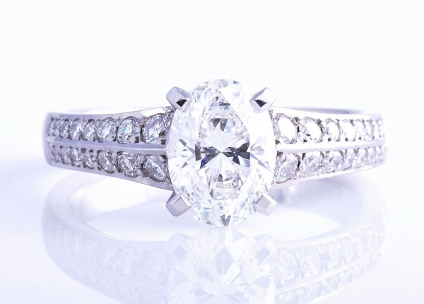 1.5ct brilliant cut oval diamond ring. Four claw setting with two rows of pave diamonds set into the band